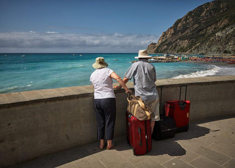 Casal olhando o mar com malas de viagem.