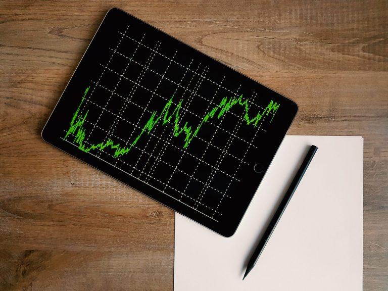 Tablet mostrando gráfico com papel ao lado.
