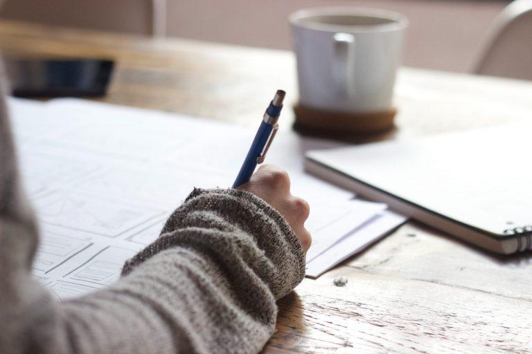 Braço de mulher escrevendo em papéis.