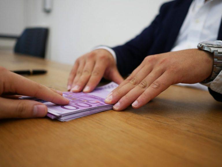 Homem entregando notas de dinheiro para outra pessoa.