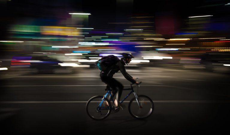 Imagem mostra um homem pedalando em alta velocidade numa rua, à noite, com luzes e e carros deformados e desfocados ao fundo.