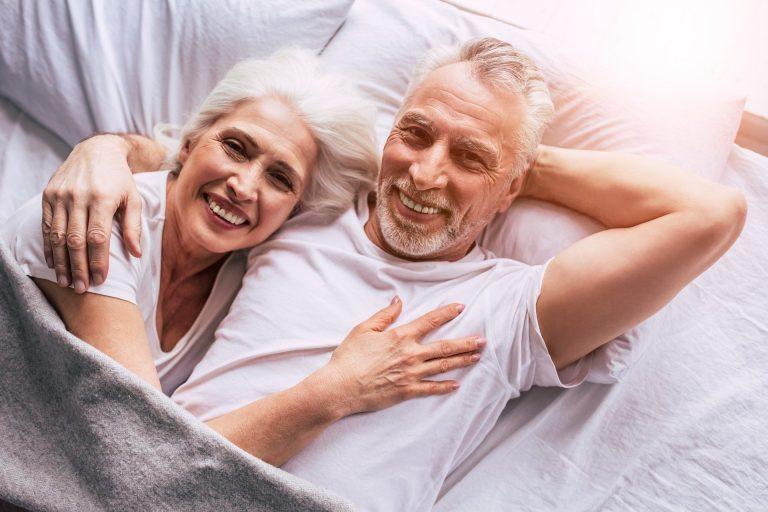 Imagem de um casal idoso abraçado.