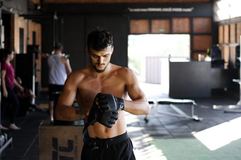Imagem mostra um homem numa academia, ajustando a luva do UFC de sua mão direita.