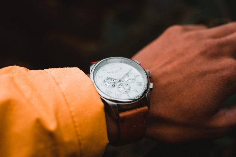 Imagem mostra um close um relógio de pulso analógico com respingos de água em sua superfície, assim como na mão que o usa.