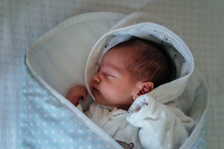 Bebê dormindo em saco de dormir.