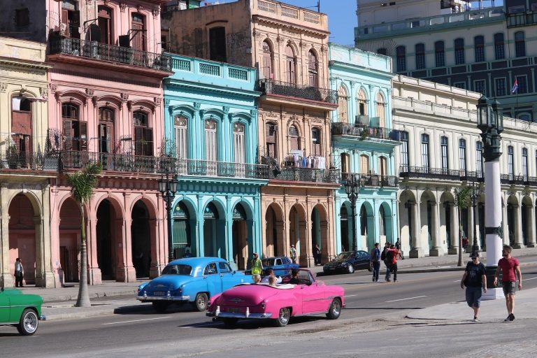 Uma rua de Cuba com prédios e carros.