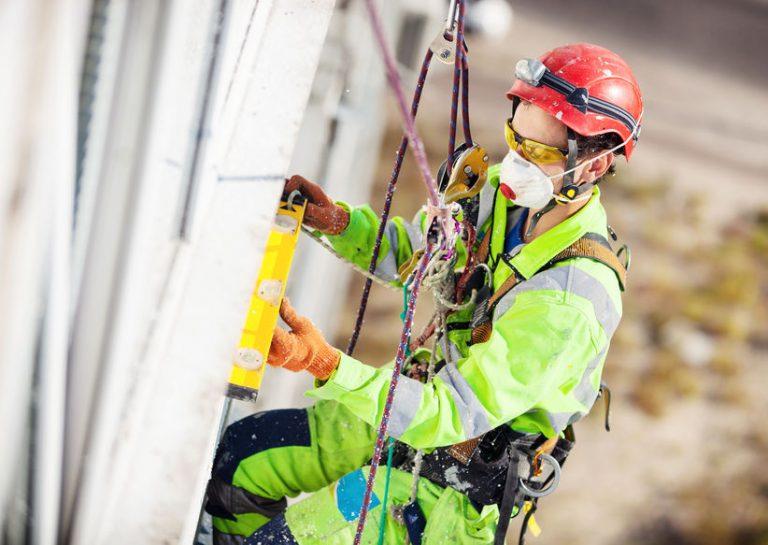 Imagem mostra um trabalhador pendurado enquanto usa um talabarte.