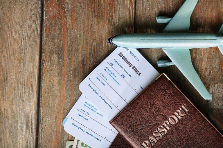 Passaporte, passagens e avião em miniatura.