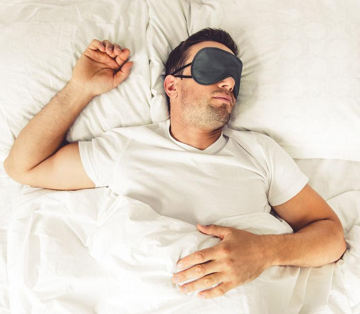 Homem deitado de barriga para cima com máscara de dormir.