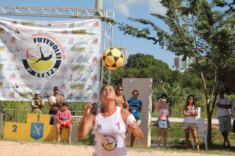 Imagem mostra uma atleta cabeceando a bola, sob um sol forte. Ao fundo, espectadores e um grande banner que anuncia a primeira etapa de um torneio de futevôlei.