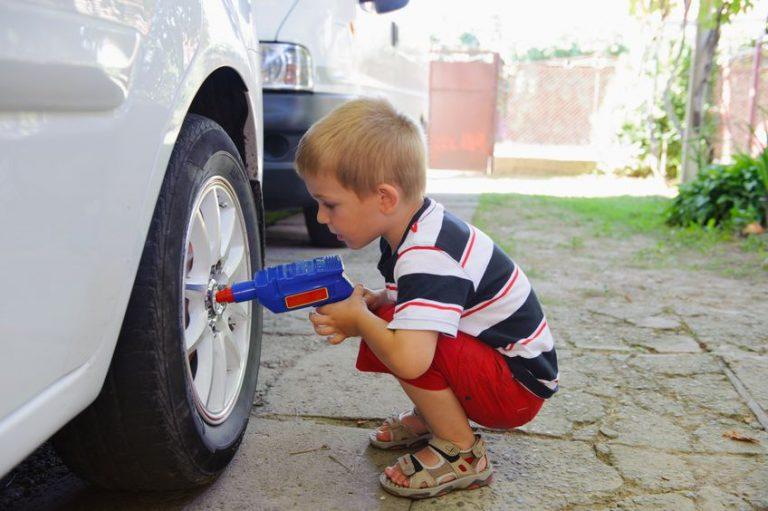 Menino brincando com furadeira de brinquedo em roda de carro.