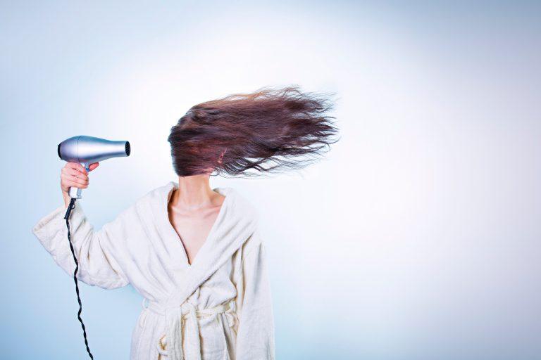 Mulher vestindo um roupão, apontando o secador para os cabelos que voam para o lado cobrindo o seu rosto.