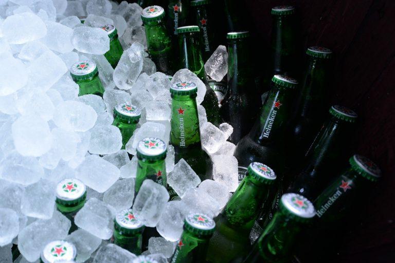 Imagem mostra um close de várias garrafas de cerveja entre um grande monte de pedras de gelo.
