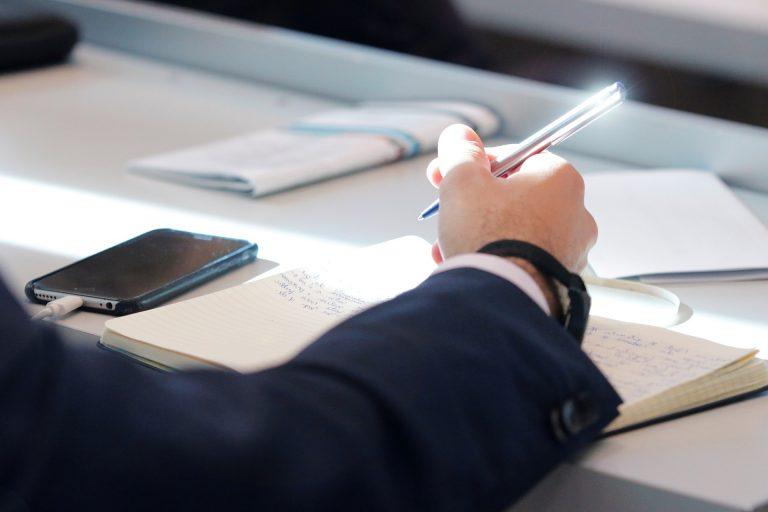 Homem de terno escrevendo em papel com celular ao lado.