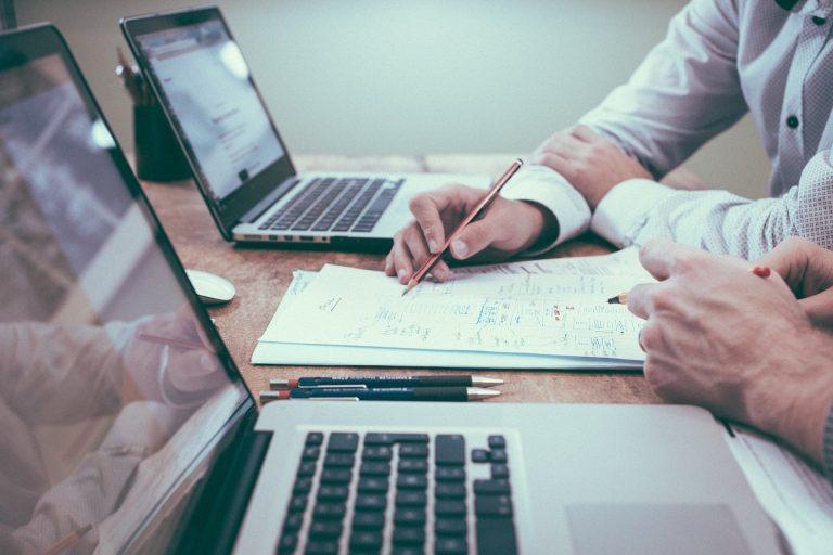 Dois homens analisando dados numéricos no papel com notebooks abertos.