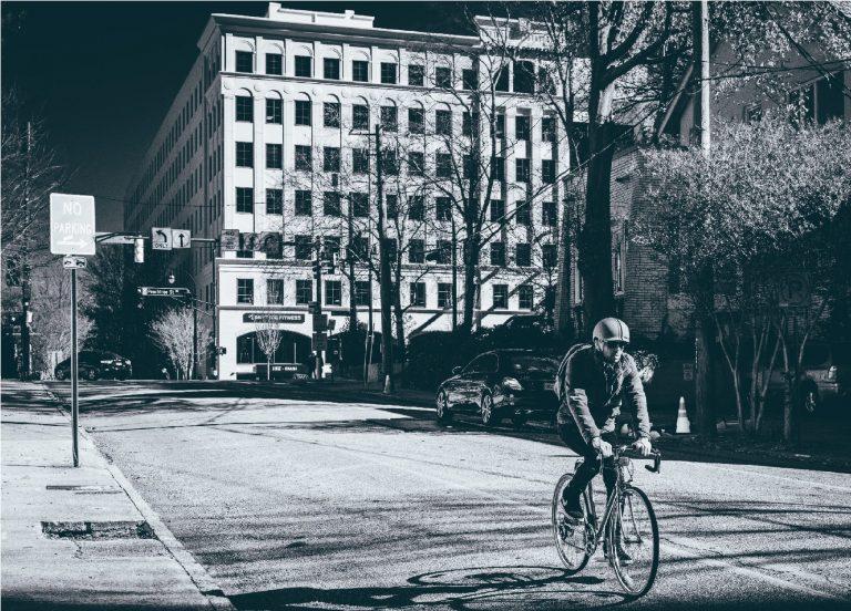 Imagem em preto e branco mostra um homem pedalando uma bicicleta numa rua vazia, com apenas um carro estacionado e outro virando a esquina, ao fundo.