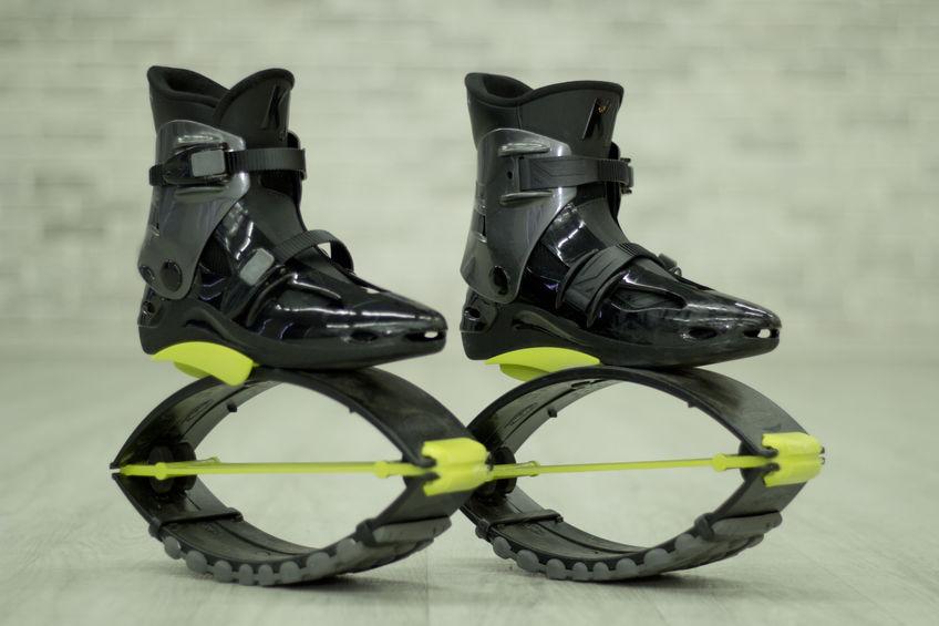"""Imagem mostra um par de Kangoo Jumps """"desocupados"""", de botas pretas e detalhes em amarelo sob um piso liso."""