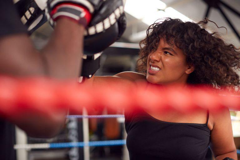 Imagem mostra o close de uma mulher dentro de um ringue, golpeando uma luva aparadora, desfocada no quadro.