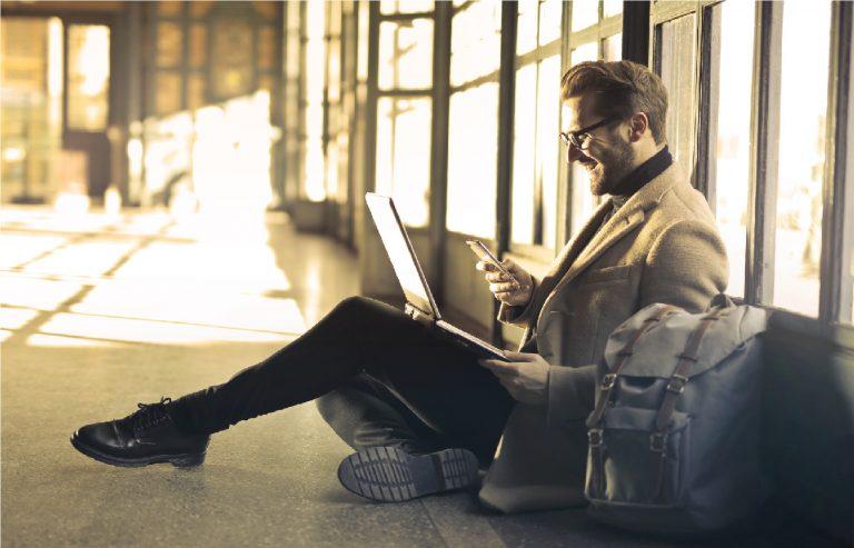 Na foto um homem sentado no chão com um notebook no colo e uma mochila ao lado.