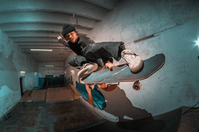 Imagem mostra um skatista no ar, no momento em que faz uma manobra. Ao fundo, é possível ver toda a pista, vazia, com apenas um skate ao fundo.