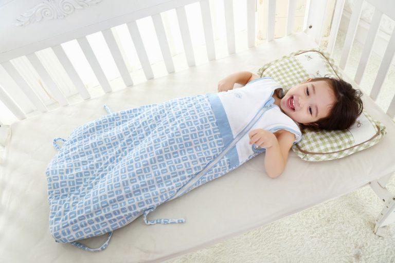 Menina com saco de dormir no berço.