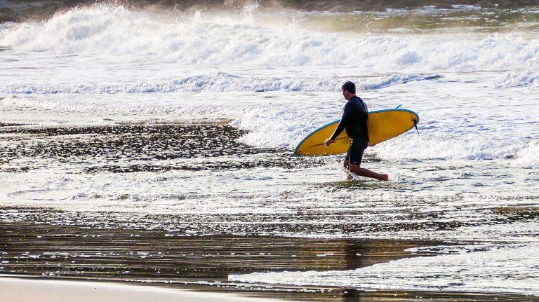 Surfista caminhando segurando a prancha e mar ao fundo.