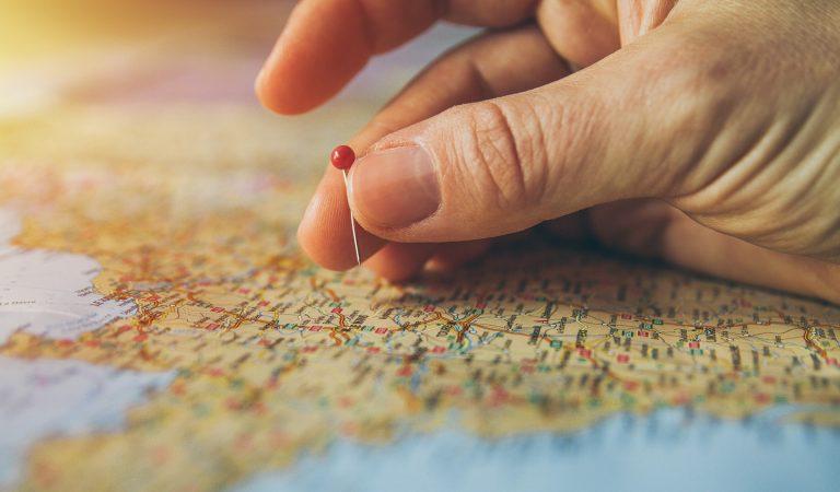 Pessoa colocando pin no mapa mundi.