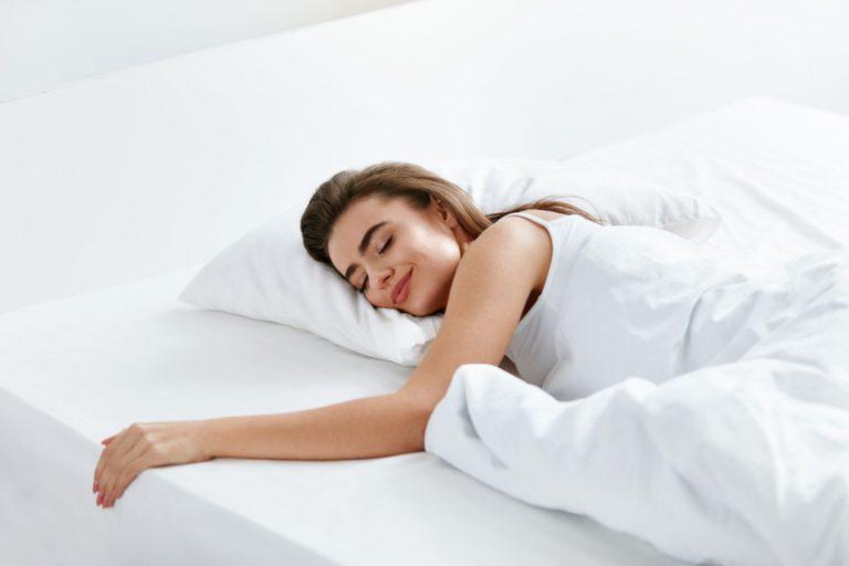Mulher dormindo de bruços em cama com roupas de cama brancas.