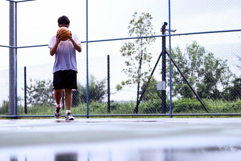 Imagem mostra uma bola de basquete da Spalding, com o logo da NBA voltado para a câmera, sobre um fundo escuro.