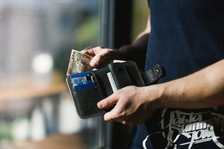 Imagem de um homem colocando dinheiro dentro de uma carteira em estilo bifold