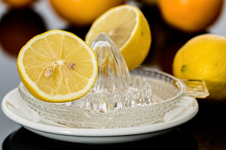 Imagem de laranja cortada sobre extrator de suco de plástico transparente