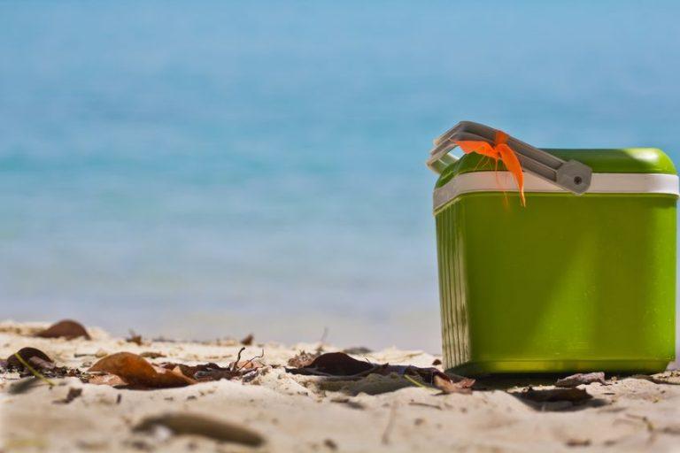 Imagem mostra uma caixa térmica fechada sobre a areia de uma praia. Ao fundo, é possível ver o azul do mar, desfocado.