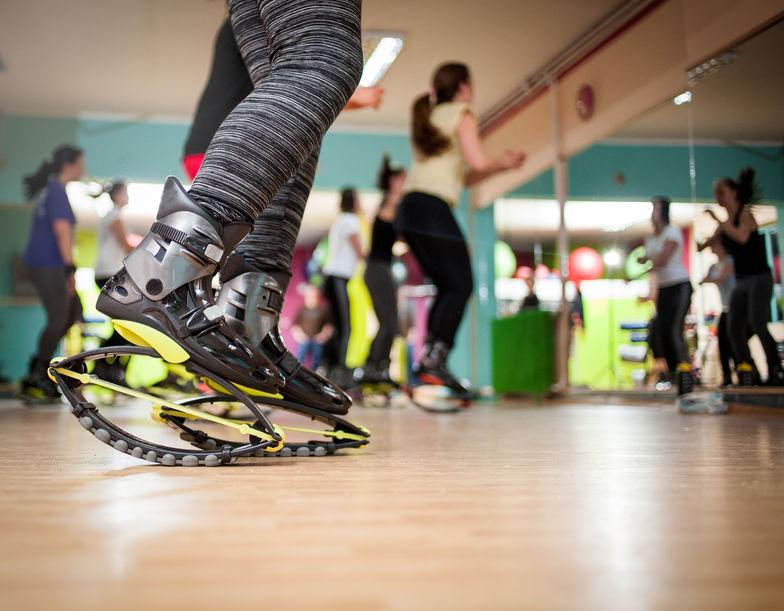 Imagem mostra o close de uma mulher, retratada apenas por suas pernas, usando um par de Kangoo Jumps durante uma atividade numa sala de academia.