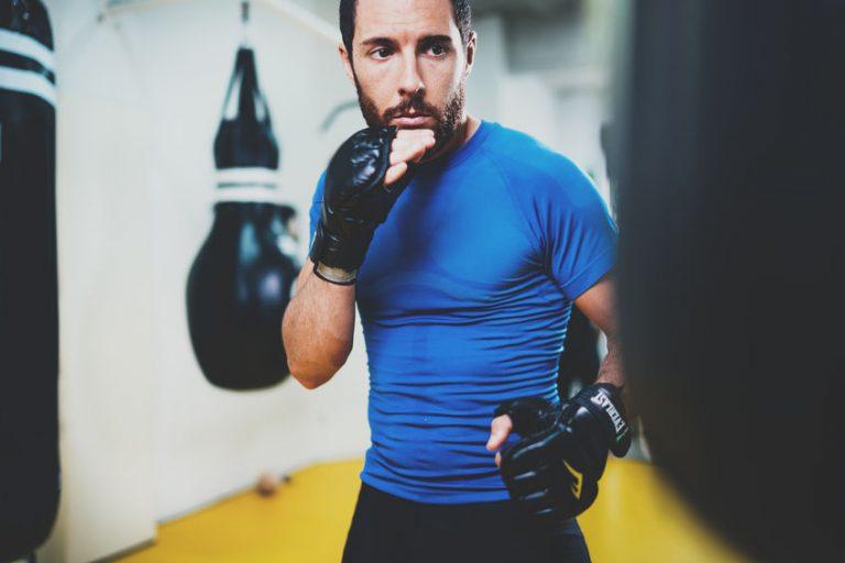 Imagem mostra um homem treinando com luvas de MMA e um saco de pancadas, este desfocado no quadro, dentro de uma academia.