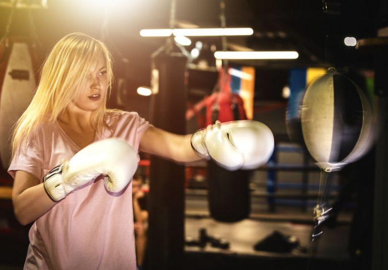 Imagem mostra uma lutadora dentro de uma academia, prestes a golpear uma punching ball suspensa.