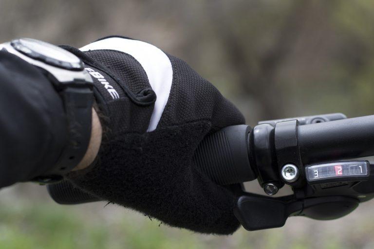 Imagem mostra um close de uma mão, com uma luva, segurando o guidão de uma bicicleta. Essa mesma mão usa um relógio, que está fora do foco.