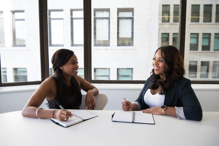 Duas mulheres conversando em mesa de trabalho.