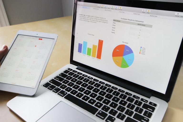 Notebook e pessoa segurando tablet com imagem de calendário.