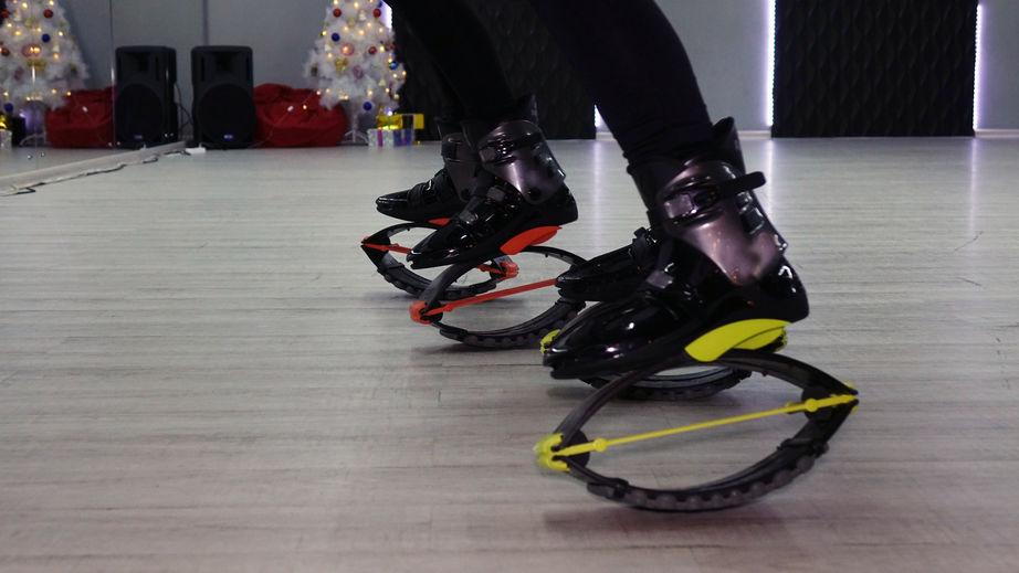 Imagem enquadra os pés de duas pessoas, que, lado a lado e de frete para um espelho, calçam seus respectivos pares de Kangoo Jumps