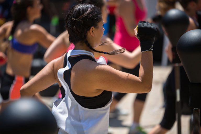 Imagem mostra uma mulher, de costas para a câmera, durante um exercício com uma punching ball com base.