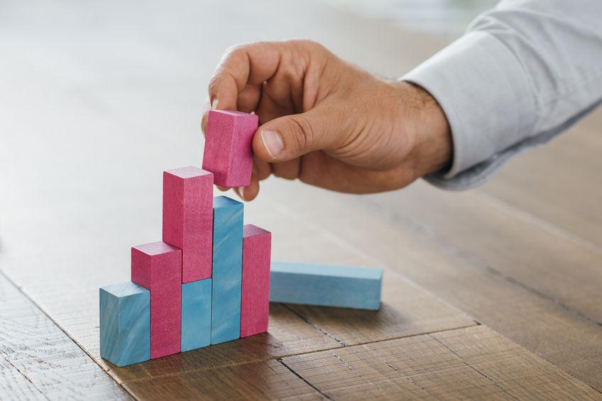 Mão masculina encaixando blocos de montar reproduzindo um gráfico.