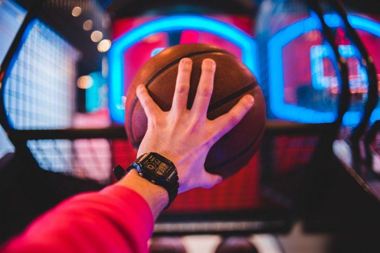 Imagem mostra um braço, com um relógio digital no pulso, segurando uma bola de basquete na mão. Ao fundo, é possível distinguir as luzes de uma tabela de basquete.