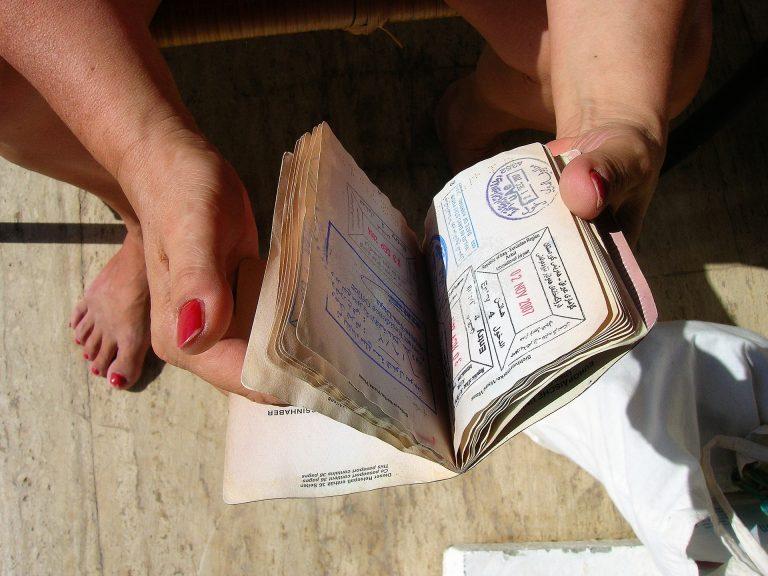Mulher mostrando folhas carimbadas do passaporte.