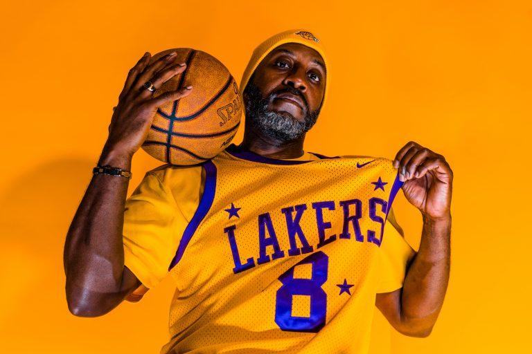Imagem mostra um homem de touca e barba grisalha, ostentando uma camisa do Los Angeles Lakers. A mão esquerda pinça um pedaço da camisa, enquanto a direita apoia uma bola Spalding no seu ombro direito.