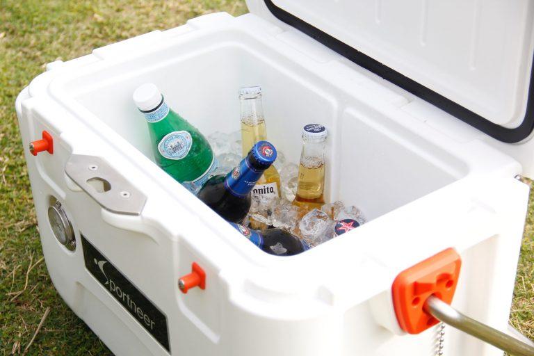 Imagem mostra o interior de uma caixa térmica, com garrafas de bebidas diversas, cobertas parcialmente por pedras de gelo.