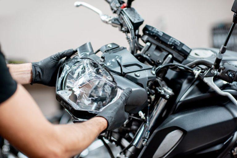 Imagem mostra a parte frontal de um guidão de bicicleta, equipado com um farol do tipo cat eye.