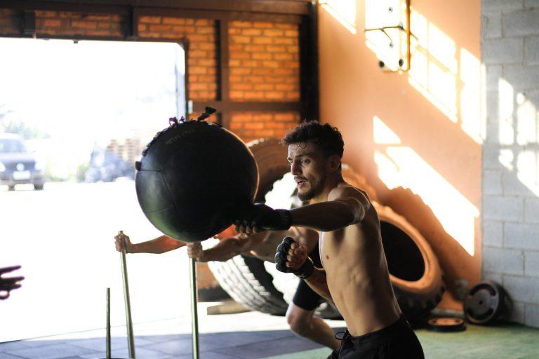 Imagem mostra um lutador dentro de uma academia, golpeando uma grande punching ball suspensa.