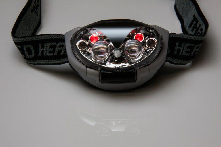 Imagem mostra um farol de bike avulso sobre uma superfície lisa e reflexiva, com duas pequenas luzes vermelhas acesas.