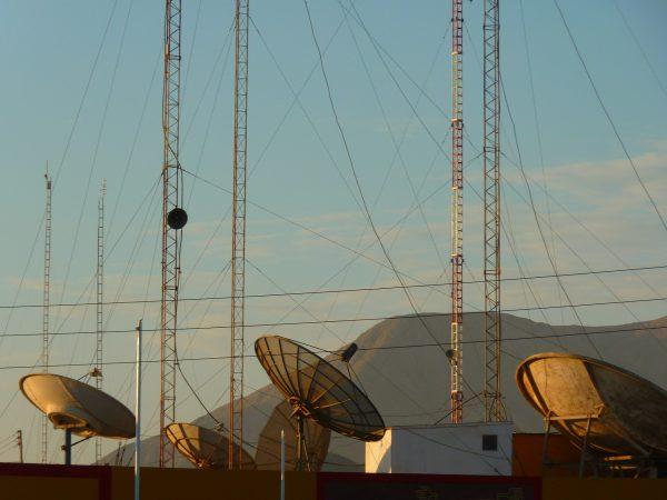 Imagem com várias antenas parabólicas ao lado uma das outras, diversas torres de comunicação e muitos fios ao redor das torres.