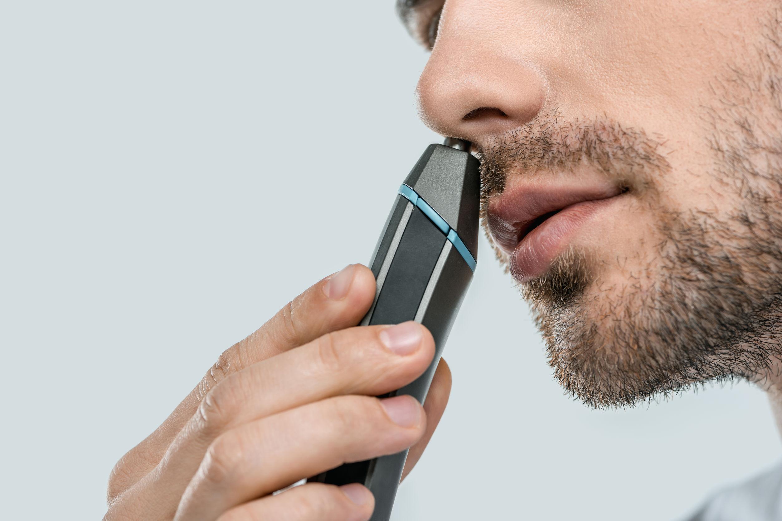Imagem mostra um homem usando um aparador de pelos do nariz.